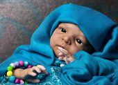 picture of baby doll  - African American Baby Doll Portrait lying under turquoise blanket - JPG