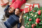 High angle view of young man and african woman lying on floor near christmas tree with presents. Top poster