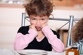 Sulky girl sitting at the breakfast table