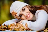 A portrait of a beautiful young woman sitting at a table covered with golden autumn leaves. Lifestyl poster