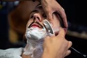 Razor In Hands Of Specialist Barber. Barber Shaving A Man In A Barber Shop, Close-up. Man Having A S poster