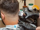 Stylist Cutting Hair On Males Nape In Barbershop, Close Up View. Stylists Hands In Black Rubber Glov poster