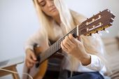 Beautiful Young Woman Playing Guitar While Sitting On The Bed At Home. Portrait Of Cute Girl In Casu poster