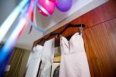 The Bride S Main And Spare Dress Hangs On The Front Of The Wardrobe, And Next To The Ceiling There A poster