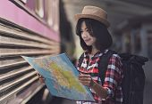 Young Asian Woman Traveller Is Looking At The Map At The Train Station, Travel And Transportation Co poster