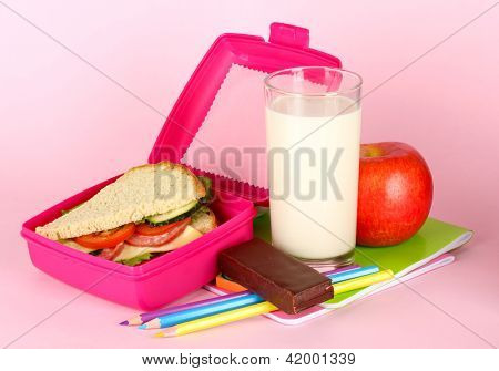 Lunch box with sandwich,apple,milk and stationery on pink background