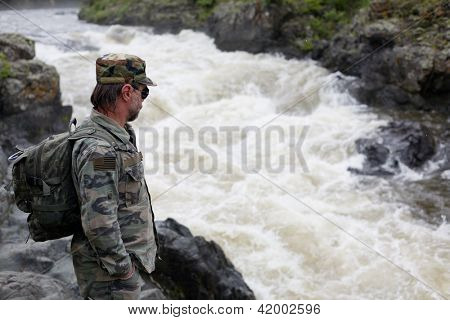 Hiker on the shore of a mountain river. Russia. Primorskiy kray. Kema river.
