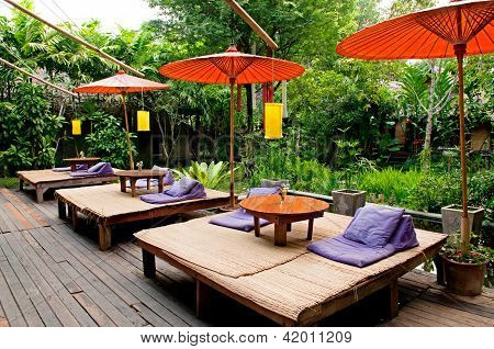 Traditional Thai Umbrella And Relaxation Bed Near The Garden