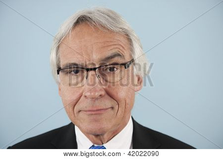 suspicion: Senior businessman thinking with serious looks and raised eyebrow