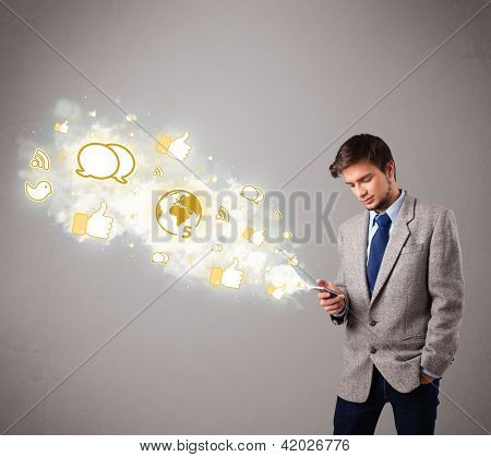 attractive young man holding a phone with social media icons in abstract cloud