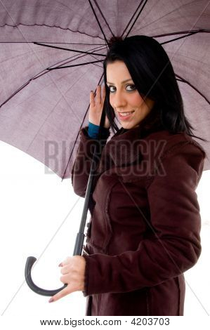 Side View Of Smiling Woman Holding Umbrella On White Background