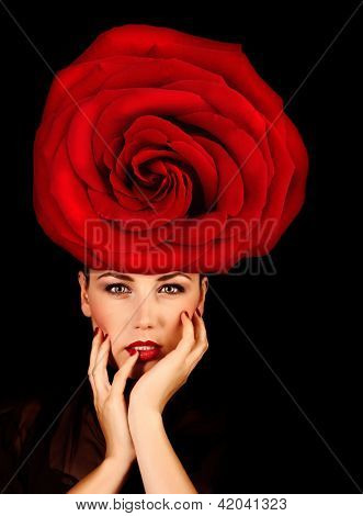 Picture of attractive female wearing stylish floral hat, fashionable accessories, portrait of pretty woman with great red rose on the head isolated on black background, Valentine day, love concept