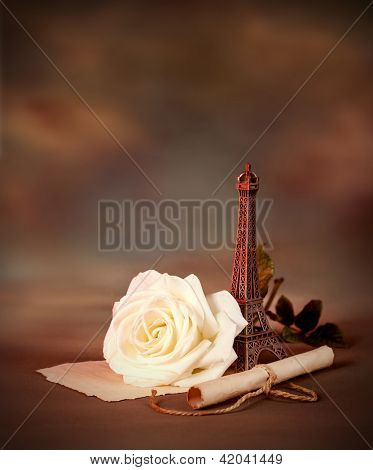 Photo of beautiful romantic still life on dark grunge background, love letter, old paper scroll with romantic message decorated with small Eiffel tower, Valentine day in Paris, honeymoon in France