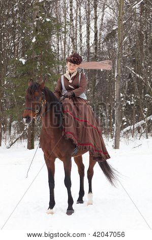 Eleganny woman in riding habit sits astride a bay Arab racer
