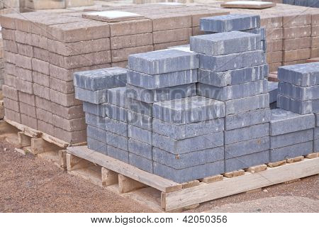 Stacks of various colored concrete pavers (paving stone) or patio blocks organized on wooden pallets and for sale in a retail setting such as a garden center or building supply.