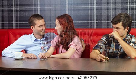 Young handsome man looking at a couple sitting in a restaurant and having fun
