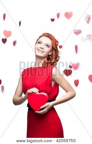 smiling red-haired girl holding red heart