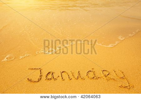 January - written in sand on beach texture - soft wave of the sea (months year series)