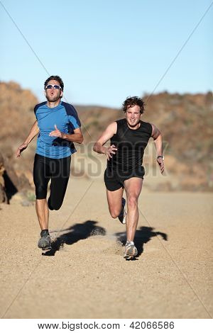 Runners. Men sprinting outdoor in extreme desert nature landscape. Two male athletes running training outside off trail.