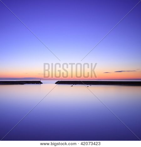 Concrete Pier Silhouette And Blue Ocean On Twilight Sunset