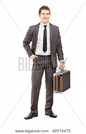 Full length portrait of a young businessman in suit holding a briefcase isolated on white background
