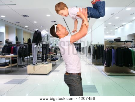 Father With Child On Hands In Clothes Shop