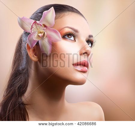 Beauty Portrait. Beautiful Stylish Girl with Orchid Flower. Pastel Colours. Perfect Face Skin