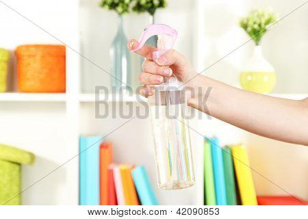 Sprayed air freshener in hand on white shelves background
