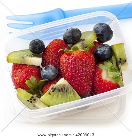 Fruit salad in a plastic lunch box, with fork.  Strawberries, blueberries and kiwi fruit.