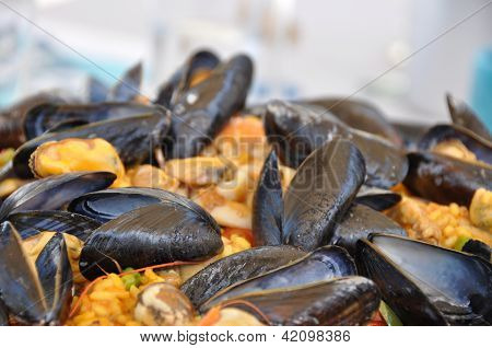 A Paella Pot With Shell Fish And Rice