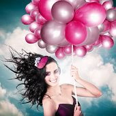 foto of fascinating  - Beautiful Smiling Australian Girl Flying High Wearing Headpiece With Balloons In A Depiction Of The Fashion Of The Field During The Melbourne Cup Spring Carnival Horse Racing Festival - JPG