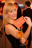 Blonde Woman Presenting Tickets For A Theatre Or Concert