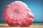 stock photo of parasailing  - Closeup of a pink parasail at the beach - JPG