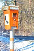 image of prone  - Orange emergency phone standing next to a dangerous and accident - JPG
