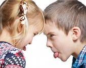 stock photo of sticking out tongue  - Sister and brother stick out tongues to each other - JPG