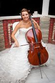picture of musicial  - Bride musicial with warm smile and beautiful eyes playing cello - JPG