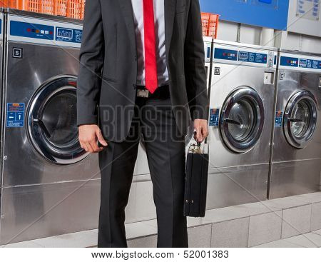 Midsection of young businessman holding suitcase in laundry