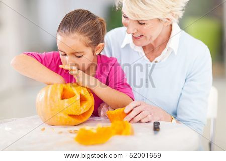 cute granddaughter helping her grandmother making halloween pumpkin at home