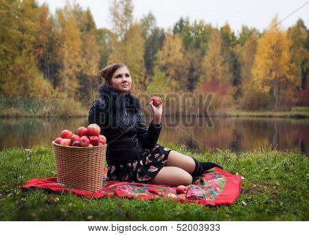 Woman at a picnic in the autumn with a basket of red apples.