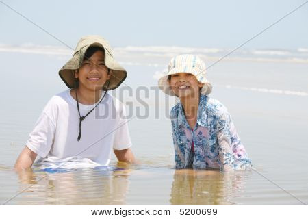Two Children Sitting In Water