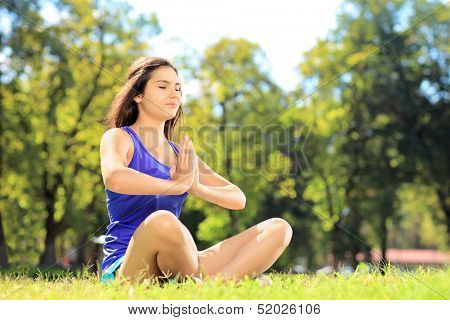 Young female athlete in sportswear doing yoga exercise seated on a grass in a park