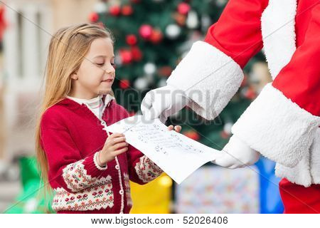 Midsection of Santa Claus taking letter from girl against Christmas tree