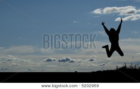 Silhouette Of A Young Joyful Man Jumping