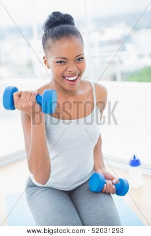 Exerted woman working out with dumbbell while looking at camera