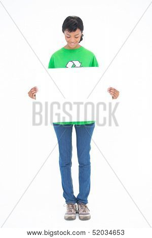 Amused black haired ecologist holding a white panel in front of her on white background