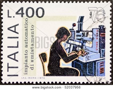 ITALY - CIRCA 1976: a stamp printed in Italy celebrates Expo Italy showing image of a woman working in mail automatic sorting system. Italy, circa 1976
