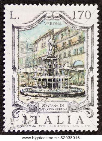 ITALY - CIRCA 1976: a stamp printed in Italy shows Fontana  Madonna Verona, built in the 14th century by Cansignorio Della Scala in Piazza delle Erbe, Verona. Italy, circa 1976