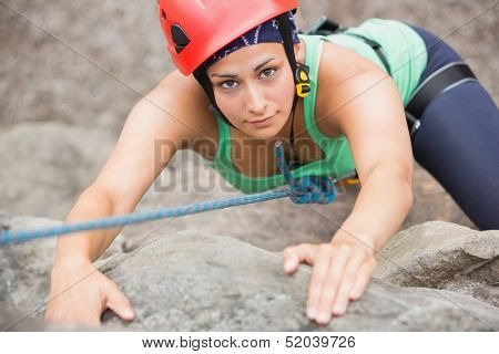 Focused girl climbing rock face looking up at camera