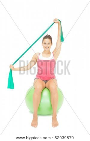 Cheery sporty brunette stretching with resistance band on white background