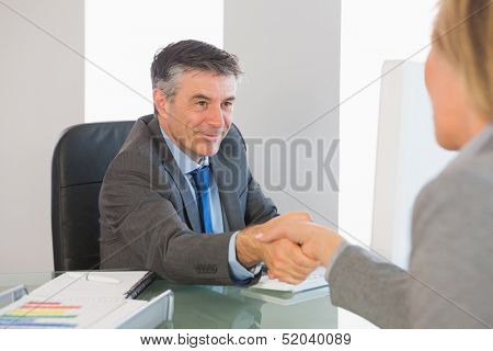 Pleased mature businessman shaking the hand of a blonde interviewee in office